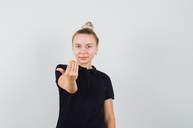 Jonge dame die uitnodigt om in zwart t-shirt te komen en er zelfverzekerd uitziet