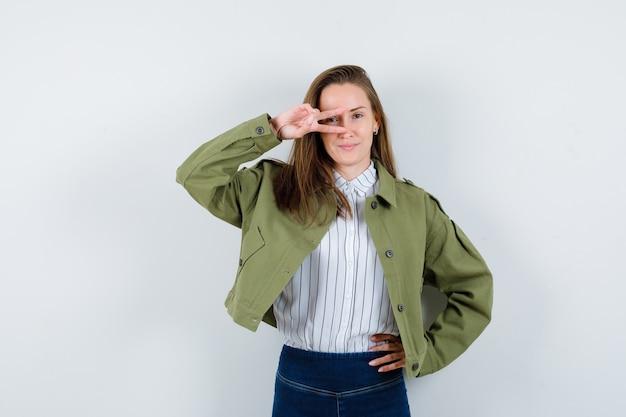 Jonge dame die v-teken op oog in overhemd, jasje toont en zelfverzekerd kijkt. vooraanzicht.