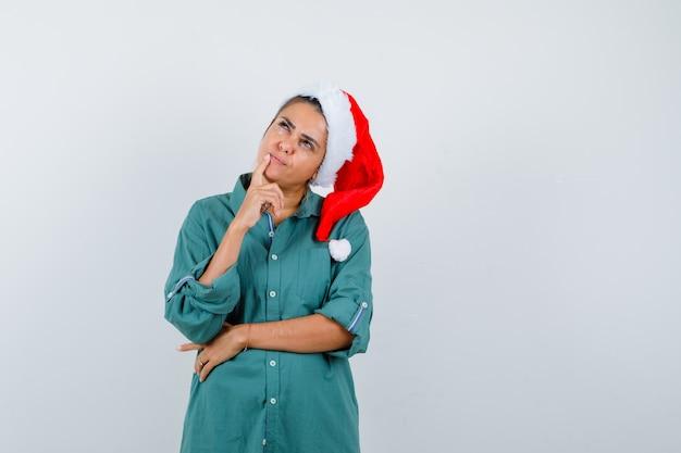 Jonge dame die vinger in de buurt van haar mond in kerstmuts, shirt aanraakt en peinzend kijkt, vooraanzicht.