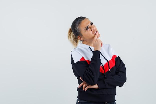 Jonge dame die vinger op mond in kleurrijk sweatshirt houdt en verloren kijkt. vooraanzicht.