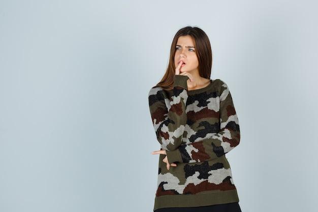 Jonge dame die vinger op mond in sweater houdt en peinzend kijkt