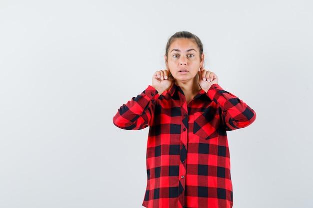 Jonge dame die vingers achter de oren in casual overhemd houdt en nieuwsgierig kijkt. vooraanzicht.