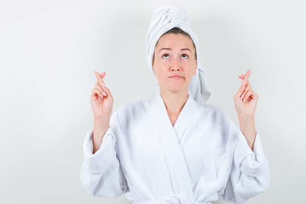 Jonge dame die vingers gekruist in witte badjas, handdoek houdt en nadenkend, vooraanzicht kijkt.