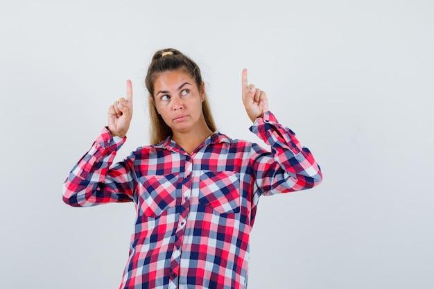 Jonge dame die vingers in geruit overhemd benadrukt en peinzend kijkt. vooraanzicht.