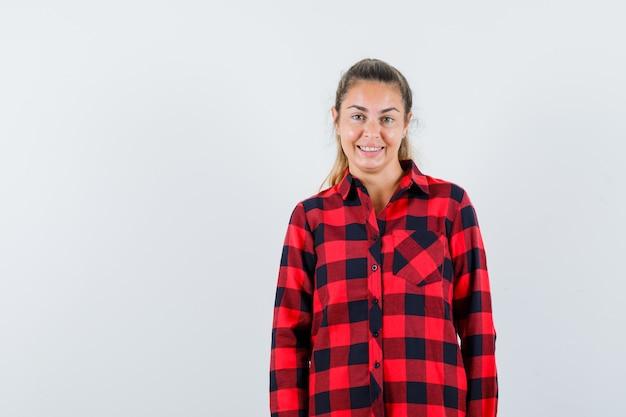 Jonge dame die vooraan in geruit overhemd kijkt en vrolijk kijkt