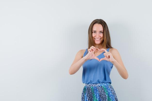Jonge dame die vredesgebaar in blouse, rok toont en lief, vooraanzicht kijkt. ruimte voor tekst