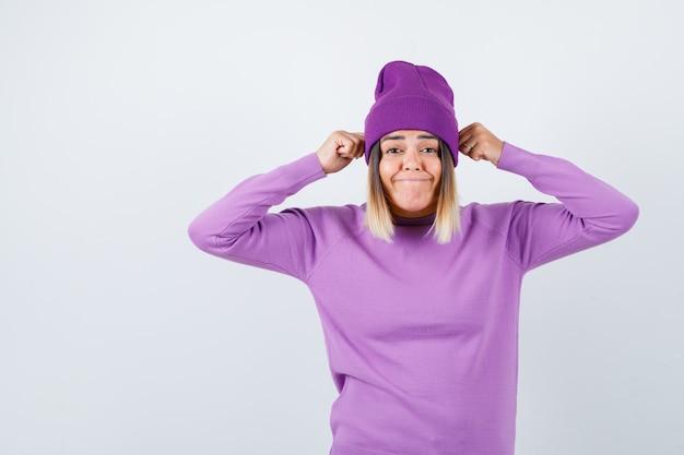 Jonge dame die vuisten op het hoofd houdt in een paarse trui, muts en er geamuseerd uitziet. vooraanzicht.