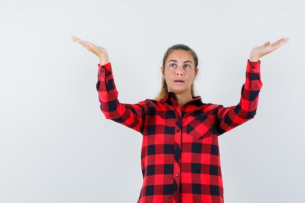 Jonge dame die wapens opheft en handpalmen spreidt in geruit overhemd en hoopvol kijkt