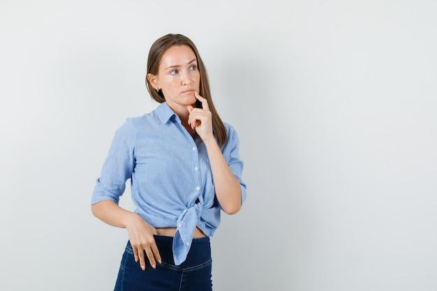 Jonge dame die weg met vinger dichtbij mond in blauw overhemd, broek kijkt en peinzend kijkt.