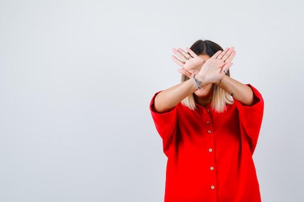 Jonge dame die weigeringsgebaar toont in een rood oversized overhemd en er zelfverzekerd uitziet, vooraanzicht.