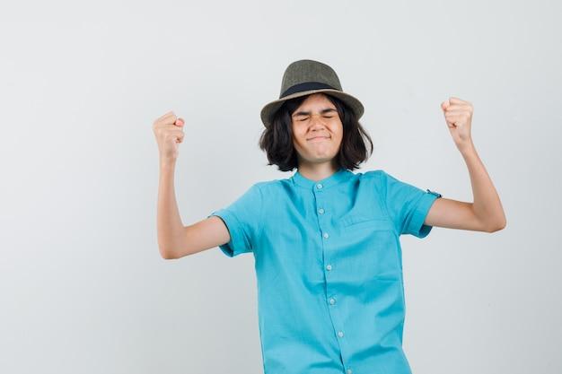 Jonge dame die winnaargebaar in blauw overhemd, hoed toont en gelukkig kijkt.