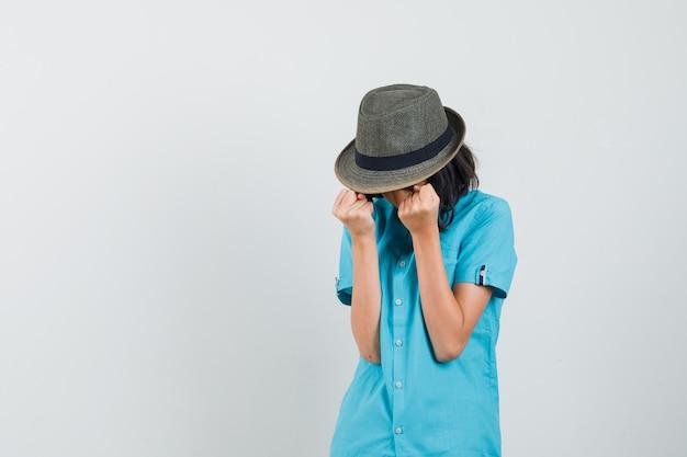 Jonge dame die winnaargebaar in blauw overhemd, hoed uitdrukt en gelukkig kijkt.