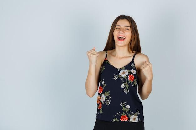 Jonge dame die winnaargebaar in bloementop toont en vrolijk kijkt