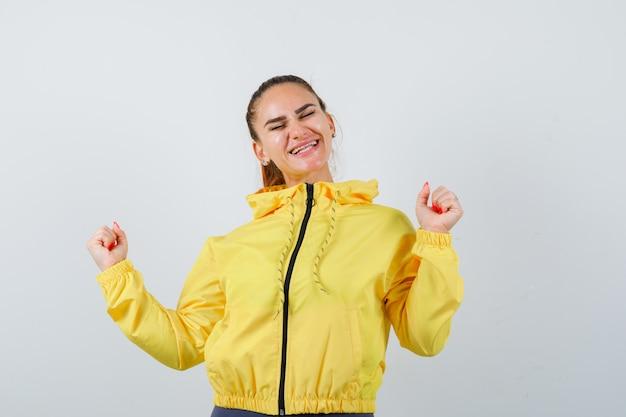 Jonge dame die winnaargebaar in geel jasje toont en gelukkig kijkt, vooraanzicht.
