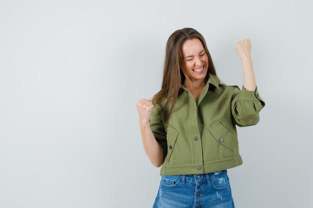 Jonge dame die winnaargebaar in groene jasborrels toont en zalig kijkt