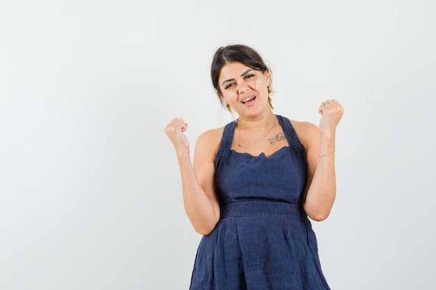 Jonge dame die winnaargebaar in jurk toont en er gelukkig uitziet