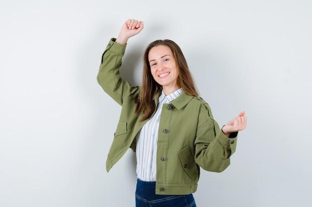 Jonge dame die winnaargebaar in overhemd, jasje toont en gelukkig kijkt. vooraanzicht.