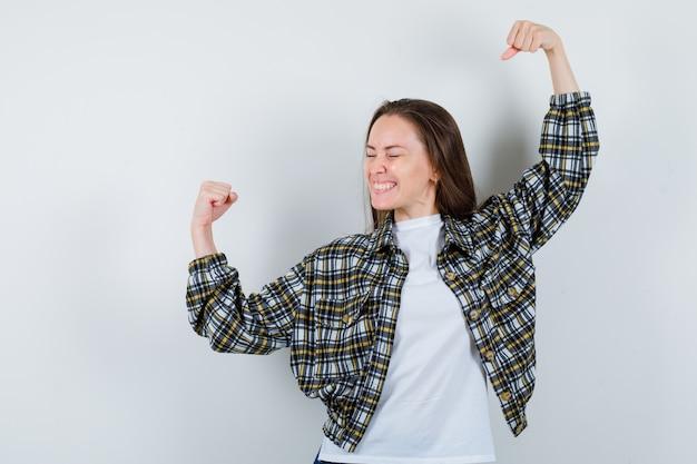 Jonge dame die winnaargebaar in t-shirt, jasje toont en zalig, vooraanzicht kijkt.
