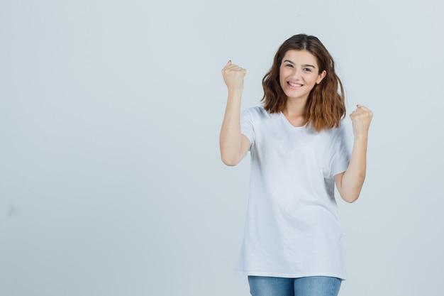 Jonge dame die winnaargebaar in t-shirt, jeans toont en gelukkig, vooraanzicht kijkt.