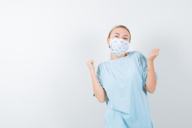 Jonge dame die winnaargebaar toont in t-shirt, masker en er gelukkig uitziet