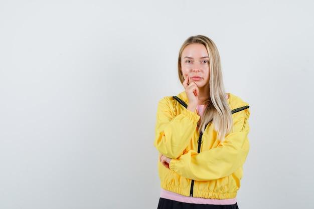 Jonge dame die zich in het denken bevindt stelt in t-shirt, jasje en peinzend kijkt