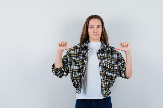 Jonge dame die zich met duimen in t-shirt, jasje, spijkerbroek richt en er trots op kijkt. vooraanzicht.