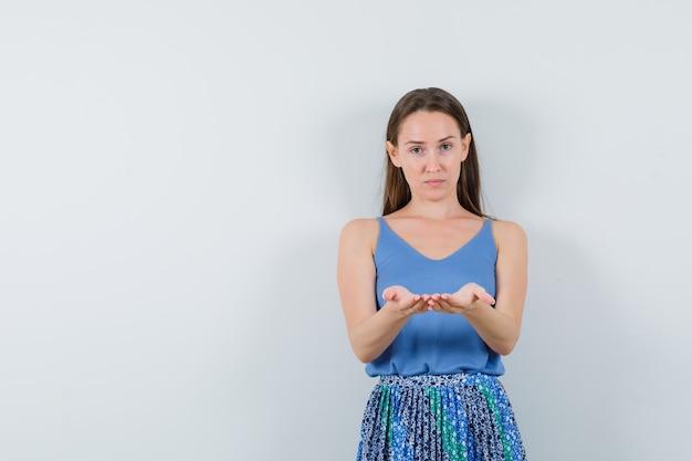 Jonge dame die zich voordeed als iets op haar handen te houden gecombineerd in blauwe blouse, rok en gefocust op zoek. vooraanzicht.