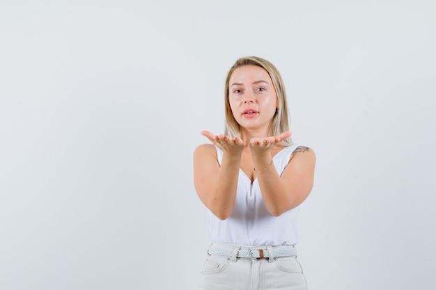 Jonge dame die zich voordeed als iets suggereren aan iemand in een witte blouse en gefocust op zoek