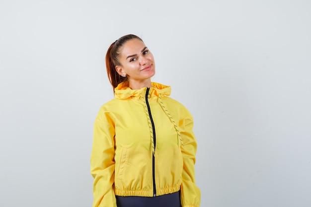 Jonge dame die zich voordeed in een gele jas en er tevreden uitziet. vooraanzicht.