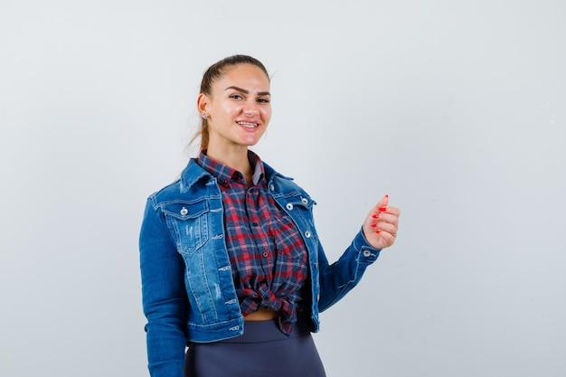 Jonge dame die zich voordeed terwijl ze de hand in het shirt, de jas steekt en er vrolijk uitziet, vooraanzicht.