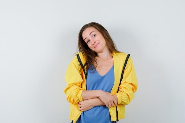 Jonge dame die zich voordeed terwijl ze het hoofd op haar schouder buigt in t-shirt, jas en er aantrekkelijk uitziet, vooraanzicht.
