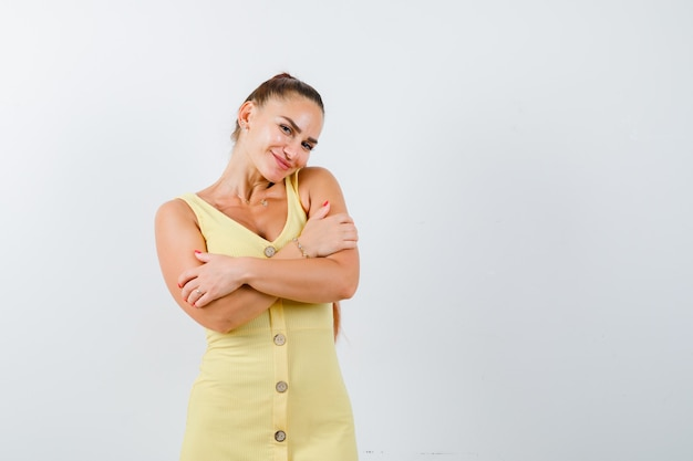 Jonge dame die zich voordeed terwijl ze zichzelf knuffelde in gele jurk en beschaamd kijkt. vooraanzicht.