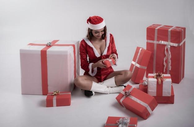 Jonge dame draagt rode jurk zit naast grote geschenkdoos en glimlach met gelukkig gevoel, model poseren