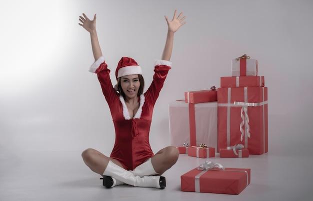 Jonge dame draagt rode jurk zittend naast geschenkdoos. handen opsteken in de lucht en glimlachen met een gelukkig gevoel, model poseren