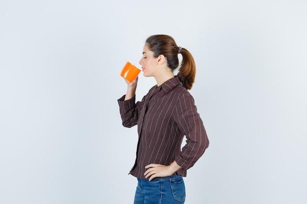 Jonge dame drinkt uit de beker, met de hand op de taille, zijwaarts in shirt, spijkerbroek en tevreden kijkend.