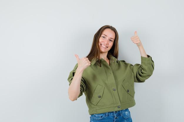 Jonge dame dubbele duimen opdagen in groene jas, korte broek en op zoek vrolijk. vooraanzicht.