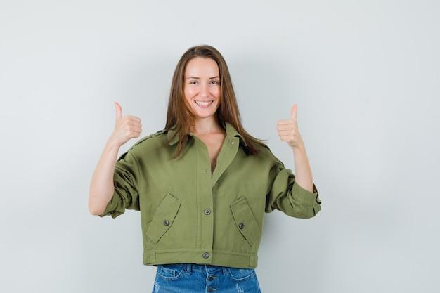 Jonge dame dubbele duimen opdagen in groene jas, korte broek en vrolijk kijken. vooraanzicht.