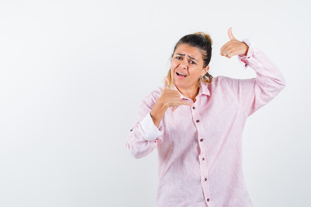 Jonge dame dubbele duimen opdagen in roze shirt en op zoek zelfverzekerd