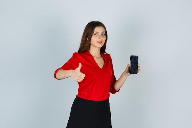Jonge dame duim opdagen terwijl mobiele telefoon in rode blouse