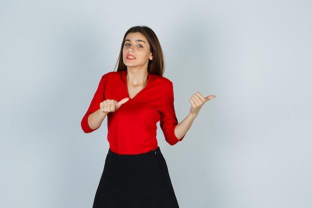 Jonge dame duimen omhoog naar de rechterkant in rode blouse, rok en aarzelend op zoek
