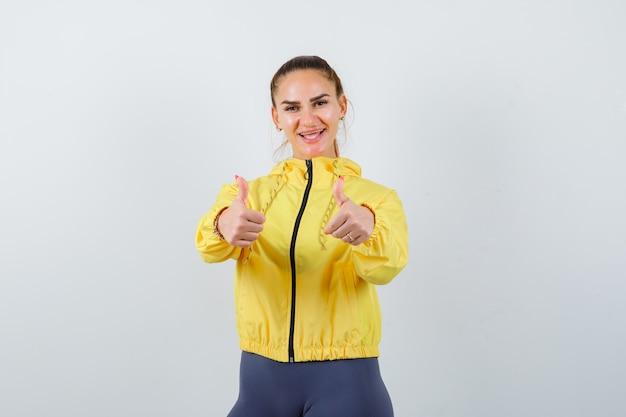 Jonge dame duimen opdagen in gele jas en vrolijk kijken. vooraanzicht.