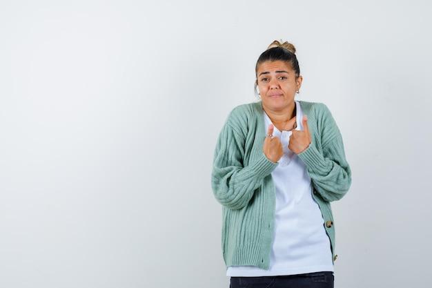 Jonge dame duimen opdagen in t-shirt, jas en zelfverzekerd kijken