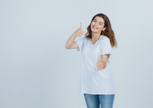 Jonge dame duimen opdagen in t-shirt, spijkerbroek en op zoek vrolijk, vooraanzicht.