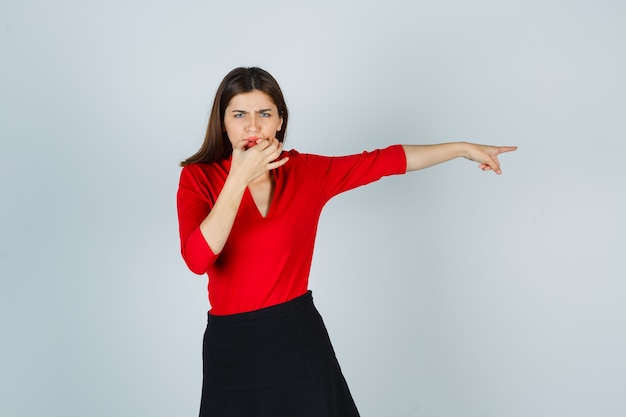 Jonge dame fluiten, rechts wijzend met wijsvinger in rode blouse