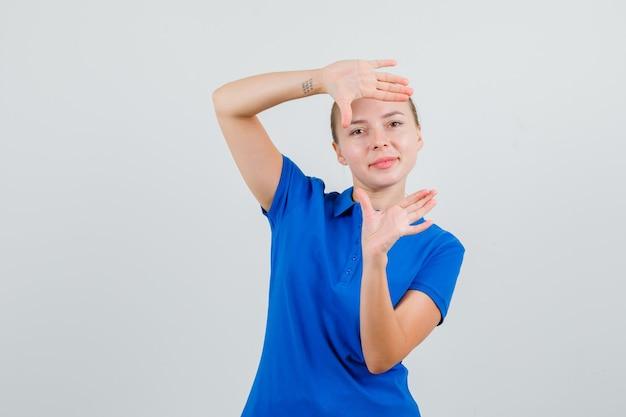 Jonge dame frame gebaar maken in blauw t-shirt en vrolijk kijken