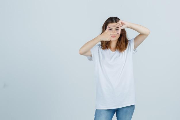 Jonge dame frame gebaar maken in t-shirt, spijkerbroek en op zoek vrolijk, vooraanzicht.