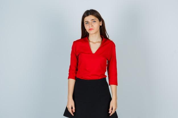 Jonge dame gebogen lippen in rode blouse, zwarte rok en teleurgesteld op zoek