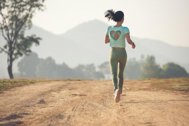 Jonge dame geniet van een gezonde levensstijl tijdens het joggen langs een landweg, lichaamsbeweging en fitness en training in de buitenlucht. jonge dame loopt op een landelijke weg tijdens zonsondergang.