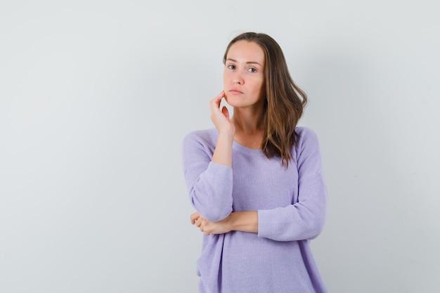 Jonge dame gezicht huid op haar wang in casual shirt aan te raken en er schattig uit te zien. vooraanzicht.