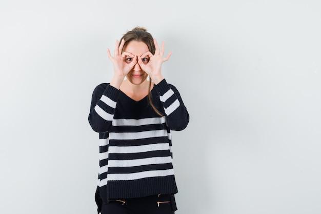 Jonge dame glazen gebaar in casual shirt tonen en op zoek grappig